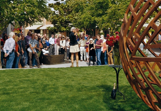 "Christiana Heinemann speaks to a crowd gathered for the dedication of ""Companion,"" a sculpture by her late husband, Bernie Hosey. Photo by Sue Misao"