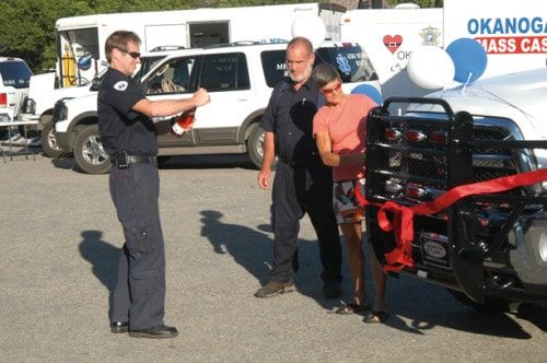 From left, paramedic Tom Smith, fleet manager Byron Braden and Aero Methow Rescue Service board president Terry Karro prepare to christen the organization's new ambulance at a community gathering last weekend. Photo courtesy of Aero Methow Rescue Service