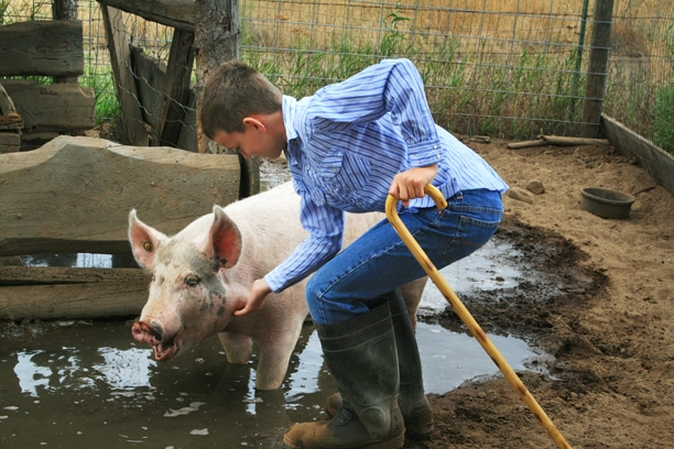 "Bodie Paul scratches his pig, Hunt, in one of Hunt's favorite spots – his chinny chin chin. ""When Hunt gets excited, he runs around and barks like a dog – it's really fun,"" said Bodie. Photo by Marcy Stamper"
