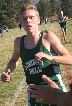 Liberty Bell's Ben Klemmeck crosses the finish line in first place, followed by Liam Daily.