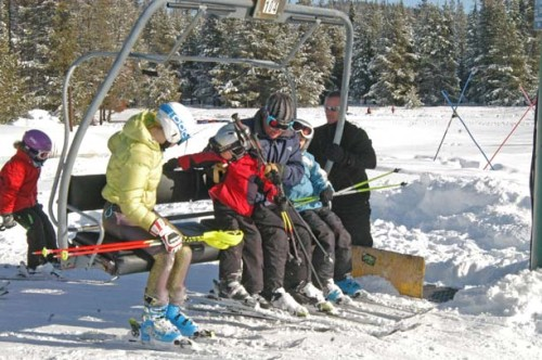 Chairlift operator Erik Olson, right, helps a group of skiers get lined up for a quad chair during the first full weekend of skiing at the Loup Loup Ski Bowl. Photo by Mike Maltais
