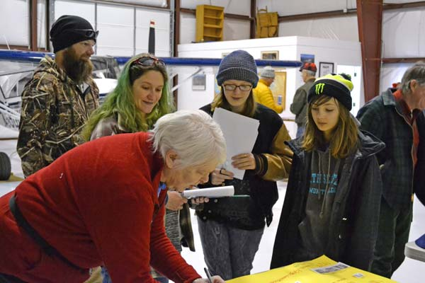 Future flyers Monica Oakes shares literature about the women aviators' organization The Ninety-Nines with Willow, right, and Chloe Temple at Aviation Day, held inside Don Fitzpatrick's hangar at the Methow Valley State Airport on Saturday. Photo by Laurelle Walsh