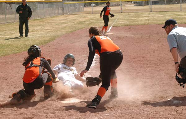 Shortstop Korrie Perryman slides into home plate in front of two Bridgeport opponents during a doubleheader against the Fillies last Saturday. The Lady Lions won both games, 16-1 and 19-4. Photo by Mike Maltais