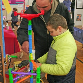 "Isaac Davis, a third-grader, shows off his experiment titled ""Chain Reaction"" that helped illustrate his investigation into Rube Goldberg's inventions. Joe Davis, Isaac's dad, was on hand to provide technical support as needed. Photo by Darla Hussey"