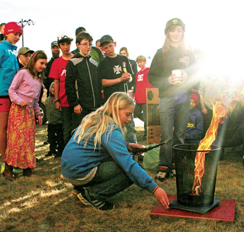 "Hanna Bakke, center, takes her ""fire tornado"" sixth-grade fire experiment out for a spin at the Methow Valley Elementary School Science Fair last Thursday. Partner Willow Temple, standing with cup, is prepared with a bit of water if things should go awry. Hannah and Willow are in the sixth grade.   Photo by Darla Hussey"