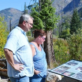 """Brian and Kristen Bruhahn, of Auburn, Washington, read one of the roadside placards that tell the story of the Thirtymile Fire, which erupted on July 9, 2001. """"You can feel a lot of people's pain at the memorial,"""" Brian said. Photo by Laurelle Walsh"""
