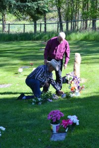 Claude Miller (kneeling) and Duffy Dufresne lay flowers at the grave of Miller's wife, Pat, who passed away last September. Photo by Laurelle Walsh