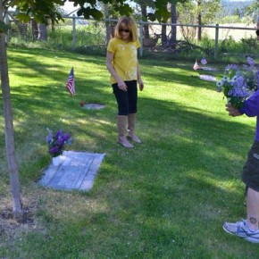 Siblings Kathy Graves Brown and Todd Graves lay a bouquet of lilacs on a family member's grave. Photo by Laurelle Walsh