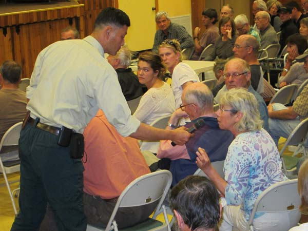 Methow Valley District Ranger Mike Liu held the microphone for Kathryn Heim at Monday's public meeting on a proposal to drill for copper deposits near Mazama. Photo by Don Nelson