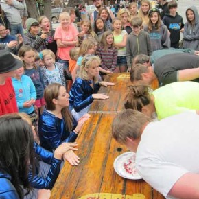 Jonathan McMillan (at nearest end of table) won the pie-eating contest for the sixth time. Photo by Don Nelson