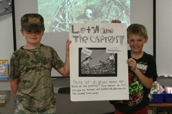 Sam Wottlin, left, and Dean Pfitzer hold one of the posters their fourth-grade class made to promote the osprey-naming contest. Photo by Marcy Stamper