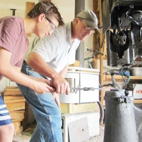 Forest Rickabaugh, left, learns how to make a hook from metal artist Jerry Merz. Photo by Don Nelson