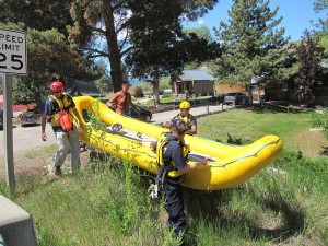 The team carries an inflatable raft down to the Chewuch River on the west side of the Highway 20 bridge. Photo by Don Nelson
