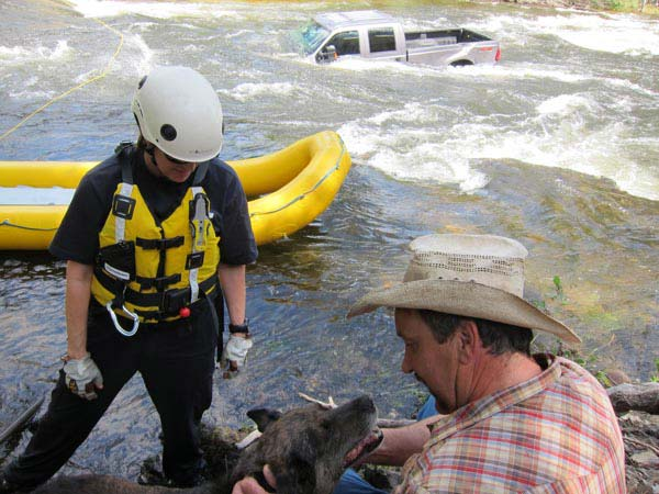 Vikki Buzzard, left, of the Swiftwater Rescue Team, watches as Jessie and her owner, Paul Picolet, reunite on shore.  Photo by Don Nelson