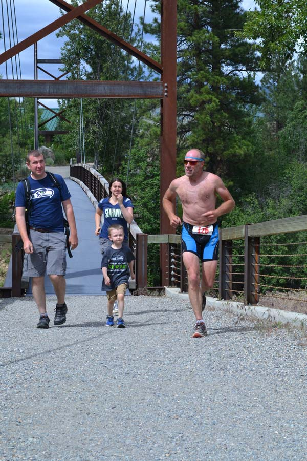 "John Spaude of Winthrop was the first iron competitor to cross the Sa Teek Wa bridge (along with some out-of-town Seahawks fans), but had to do a ""penalty lap,"" placing him in third place in the final standings with a time of 3 hours, 38 minutes. Photo by Laurelle Walsh"