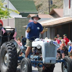 "Bob Ulrich and his tractor tow the ""Hangar Band"" to publicize the next day's Twisp Airport Fly-In. Photo by Dana Sphar"