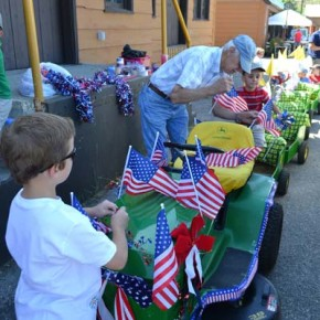 The Maxwell/Westlund family float, designed and built by Gene Westlund over the course of a winter, gets decorated for the parade by Grandpa Gene and some of the dozen grandkids who were towed behind in the six little trailers. Photo by Laurelle Walsh