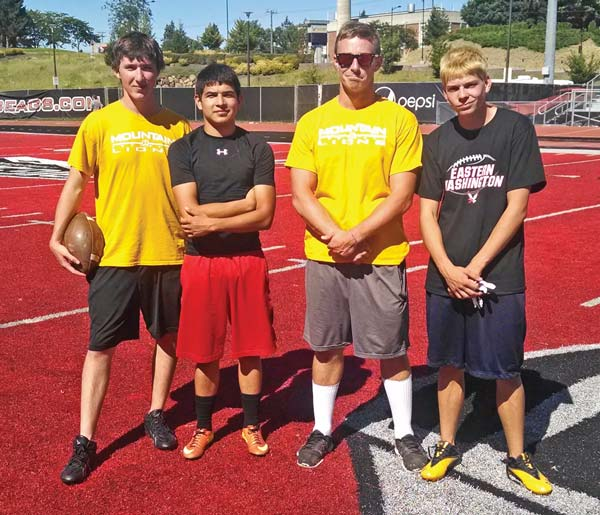 Chip Jones, left, Jorge Lara, coach Brian Wilbur and Ryan Kensrud take a moment from practice at Eastern Washington University's football camp to pose for a photo on the Inferno, the distinctive red turf surface in the EWU football stadium. Photo by Brent Walker