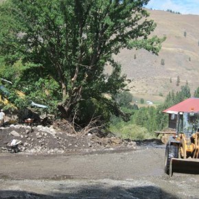 A workman cleared mud off of Highway 153; the home owned by Bob Elk and Janie Lewis is on the left. Photo by Don Nelson