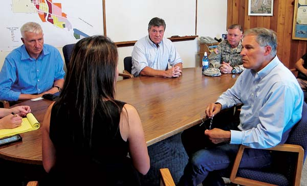 Washington Gov. Jay Inslee (right foreground), who was in the Methow Valley on Friday (Aug. 1) to talk with local officials about fire recovery efforts and assistance, met in the afternoon with Twisp Mayor Soo Ing-Moody (left foreground) and town council members. Also visiting along with Inslee were, from left at the table, Robert Ezelle, director of the state's Emergency Management Division, Bud Hover, director of the state Department of Agriculture and a Methow Valley resident, and Maj. Gen. Bret Daugherty, the state's adjutant general and head of the military department. Photo by Don Nelson