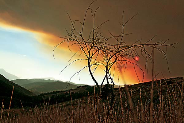 Heavy smoke rising from the Little Bridge Creek Fire tinged the sky above the Twisp River with an eerie, orange glow as more intense heat smothered the valley during the past week. Photo by Marcy Stamper