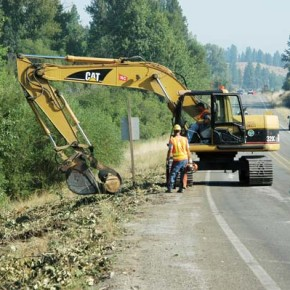 Road crews used an excavator to move debris from trees blown down along Highway 20. Photo by Ann McCreary