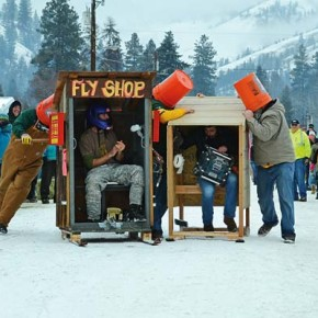 """TIght squeeze.  The Carlton Hole was one of 19 teams—and the only one from the Methow Valley—to compete in the 32nd annual Conconully Outhouse Races on Saturday (Jan. 17). Competitors came from as far away as Minnesota and Texas for the event, in which ski-mounted wooden privies, complete with toilet seat and t.p., are raced down Conconully's snow-covered main street by teams consisting of two """"pushers"""" and one """"rider."""" Here, things got a bit jammed up during the bucket race heat between Carlton Hole and Big Buck. The Carlton Hole ran hard in five divisions, but won none, despite an enthusiastic entourage of cheering Methow Valley fans. First-time team captain Jeff Lyman said, """"We've gotten the lay of the land this year, and we're going to come back next year even stronger."""" Photo by Laurelle Walsh"""