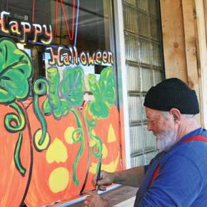 "Ed Sellers decked out Logan's Steakhouse in Twisp with some cheery jack-o'-lanterns. Sellers, who has been painting windows from Wenatchee to Oroville over the past three decades, said his designs ""come out of my fevered imagination."" .Photo by Marcy Stamper"