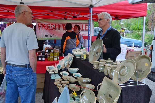 Jim Neupert's pottery display draws a shopper's interest. Photo by Laurelle Walsh