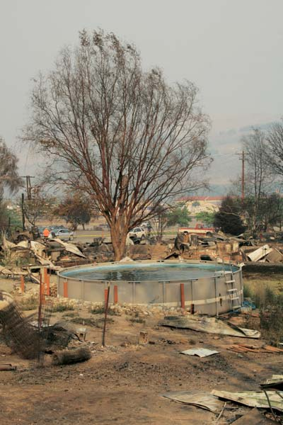 Nearly two square blocks in Pateros were obliterated when the fire descended on the town with little warning. This swimming pool resisted the flames but could not provide a buffer for nearby residences. Photo by Marcy Stamper