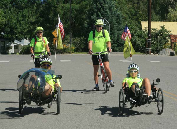 Zimmerman, left, on recumbent, who suffered a stroke almost nine years ago at age 41, and Brubaker, right, on recumbent, who sustained two traumatic brain injuries, both credit cycling—on the stable tricycles—with a their recovery of strength and balance and their increased independence. Dana and Bill Brown, rear, left to right, are accompanying the two on the cross-country ride. Photo by Marcy Stamper