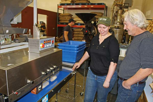 Photos by Don Nelson Blue Star production  manager Clare Williamson, left, and co-owner Dan Donohue watch the new coffee packaging machine at work.