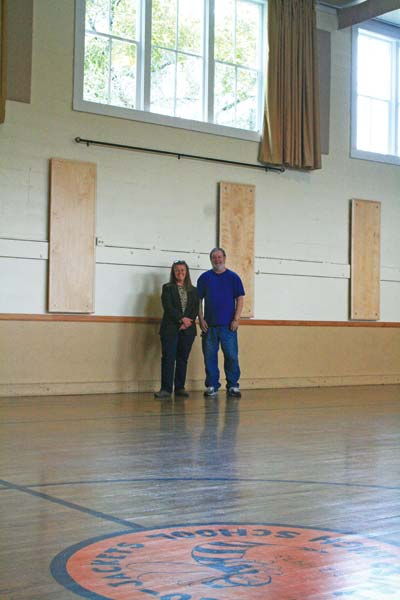 Photo by Marcy Stamper Community Center manager Kirsten Ostlie and maintenance staffer Ken Bolyard were sprucing up the gym, where more than 100 new acoustical panels were recently installed.
