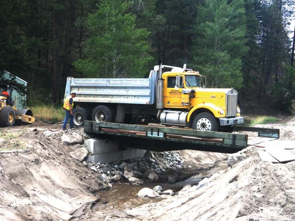 Photo courtesy Okanogan County Conservation District Michael and Valerie Sarratt's Benson Creek property was severely flooded after last summer's fires. Throughout the winter, layers of sand and ice built up along Benson Creek, threatening to push water into their house and shop. The Emergency Watershed Protection program provided for construction of a 400-foot-long crushed rock dike to divert flows away from their house. The stream channel was re-routed, which required installing a bridge to provide access to the house and garage. The Okanogan Conservation District will help revegetate the stream banks and pasture areas.