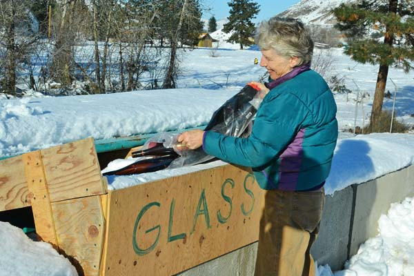 Kathy Carney uses the new glass system at Methow Recycles. Photo by Laurelle Walsh